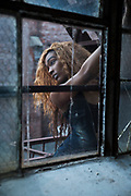 A black woman hangs on to a fire escape as seen through a cracked window.