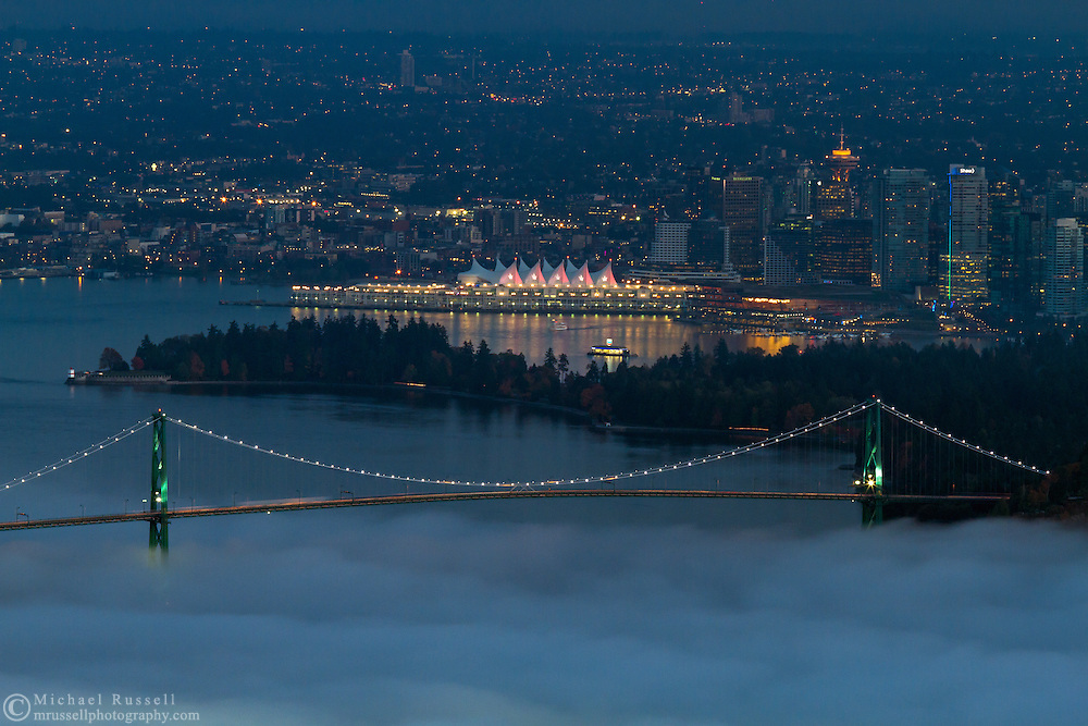 View of the Lions Gate Bridge, Stanley Park and downtown Vancouver as the fog rolls in from English Bay to Burrard Inlet.  Photographed from the Cypress Lookout at Cypress Provincial Park in West Vancouver, British Columbia, Canada