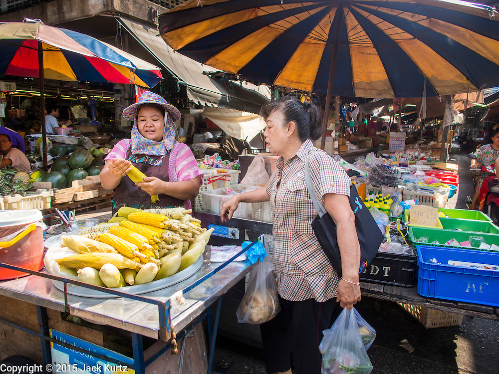 20 APRIL 2015 - BANGKOK, THAILAND:  A women sells freshly grilled sweet corn to a customer in Talat Phlu market in the Thonburi section of Bangkok.    PHOTO BY JACK KURTZ
