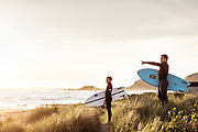 Surfers standing in the sand dunes watching the surf at St Ouen's Bay, Jersey at sunset