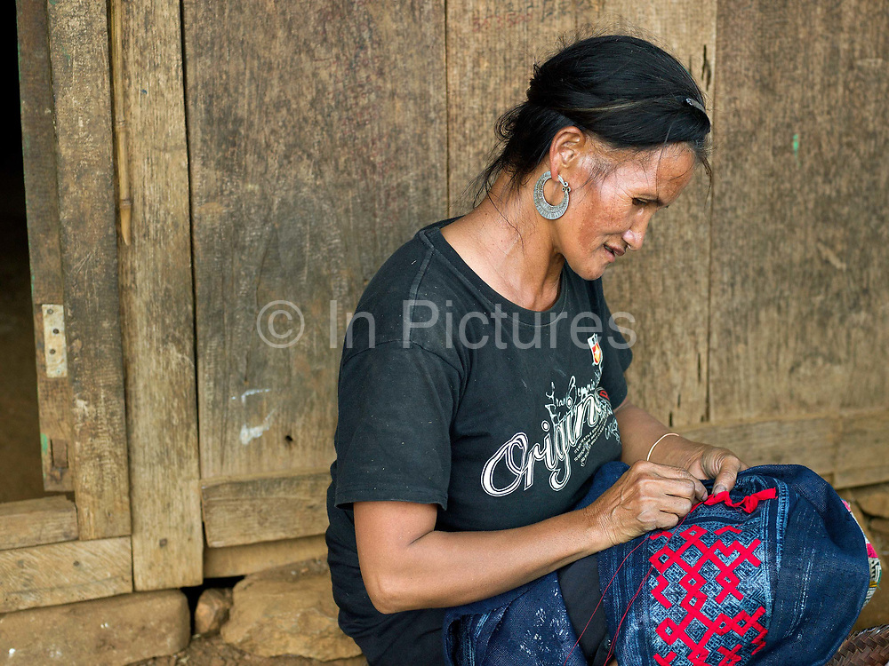 A Hmong woman sewing her traditional skirt, Ban Long Kuang, Houaphan province, Lao PDR. The woven hemp fabric is decorated by batik, a wax resist technique which is the basis for red cotton applique and colourful cross stitch embroidery.