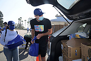 No Vet Left Alone/Life Aid Research founder John Wordin distributes meals during Los Angeles Dodgers Foundation 16th annual Thanksgiving Turkey Giveaway at Dodger Stadium, Thursday, Nov. 19, 2020, in Los Angeles.