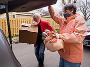 "06 APRIL 2020 - DES MOINES, IOWA: LAURIE HICKS and LARRY CLAUSON, both volunteers, bring boxes of food to a family in a car during a drive up emergency food distribution at First DSM Church in Des Moines. Volunteers brought food to the people in the cars to maintain proper ""social distancing."" On Monday, 06 April, Iowa reported 946 confirmed cases of the Novel Coronavirus (SARS-CoV-2) and COVID-19. There have been 25 deaths attributed to COVID-19 in Iowa. Most non-essential businesses are closed until 30 April. Well over 100,000 Iowans filed first time claims for unemployment in the last three weeks, more than applied during the peak of the Great Recession of 2008. Local food banks have seen an equal spike in people seeking nutritional assistance. First DSM Church has increased their food pantry from one day weekly to three days per week. Hundreds of people lined up Monday to get a box of food and one roll of toilet paper at the church's drive through pantry.          PHOTO BY JACK KURTZ"
