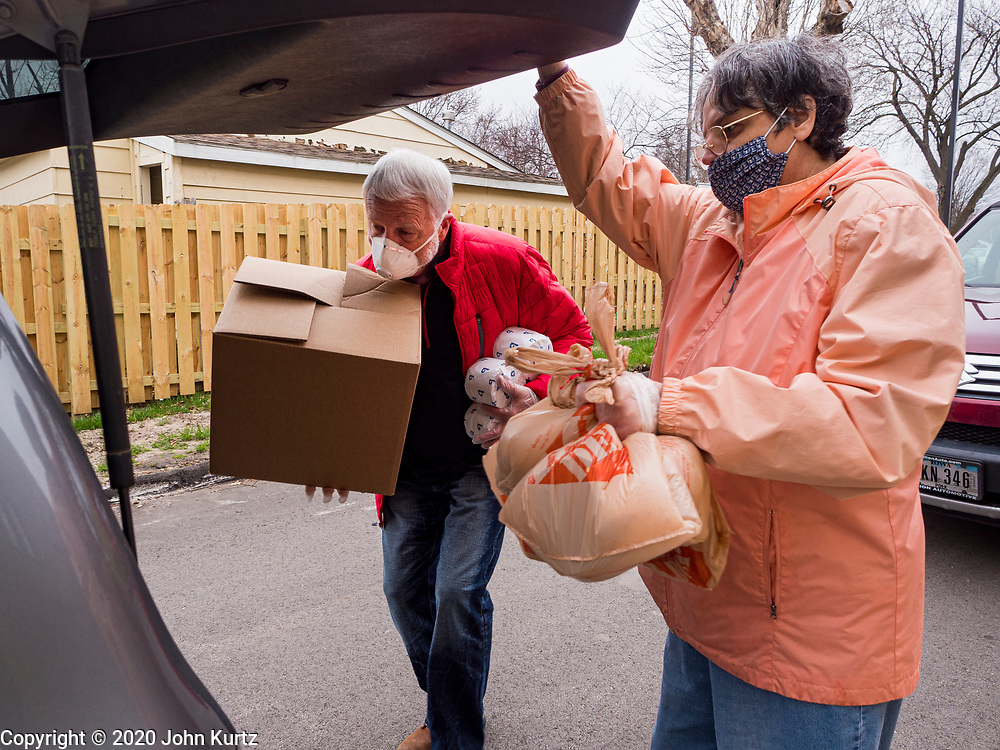 """06 APRIL 2020 - DES MOINES, IOWA: LAURIE HICKS and LARRY CLAUSON, both volunteers, bring boxes of food to a family in a car during a drive up emergency food distribution at First DSM Church in Des Moines. Volunteers brought food to the people in the cars to maintain proper """"social distancing."""" On Monday, 06 April, Iowa reported 946 confirmed cases of the Novel Coronavirus (SARS-CoV-2) and COVID-19. There have been 25 deaths attributed to COVID-19 in Iowa. Most non-essential businesses are closed until 30 April. Well over 100,000 Iowans filed first time claims for unemployment in the last three weeks, more than applied during the peak of the Great Recession of 2008. Local food banks have seen an equal spike in people seeking nutritional assistance. First DSM Church has increased their food pantry from one day weekly to three days per week. Hundreds of people lined up Monday to get a box of food and one roll of toilet paper at the church's drive through pantry.          PHOTO BY JACK KURTZ"""