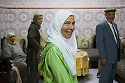 Liana Welty, an American tourist, dressed in a veil and djellaba, stands in the living room of a Moroccan family in the Meknes medina, Morocco.