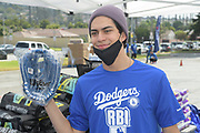 Actor Niko Guardado poses with baseball glove at the Dodger Day Drive-Thru at Belvedere Park, Tuesday, June 30, 2020, in Los Angeles. The event was hosted by The Los Angeles Dodgers Foundation, which distributed food boxes, books, sports equipment, clothing, toys and hygiene supplies to more than 1,000 registered youth from the Boyle Heights, East Los Angeles, La Puente and Monterey Park communities.