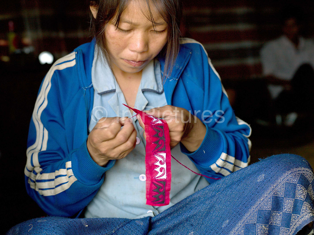 An Oma woman sewing her traditional clothing in Ban Nam Leng, Phongsaly province, Lao PDR. One of the most ethnically diverse countries in Southeast Asia, Laos has 49 officially recognised ethnic groups although there are many more self-identified and sub groups. These groups are distinguished by their own customs, beliefs and rituals. Details down to the embroidery on a shirt, the colour of the trim and the type of skirt all help signify the wearer's ethnic and clan affiliations.