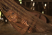 Huaorani Indian child in hammock. Gabaro Community. Yasuni National Park.<br /> Amazon rainforest, ECUADOR.  South America<br /> This Indian tribe were basically uncontacted until 1956 when missionaries from the Summer Institute of Linguistics made contact with them. However there are still some groups from the tribe that remain uncontacted.  They are known as the Tagaeri & Taromenani. Traditionally these Indians were very hostile and killed many people who tried to enter into their territory. Their territory is in the Yasuni National Park which is now also being exploited for oil.