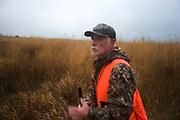 Experienced hunter Timmy Stein spots a pheasant out on the North Dakota grasslands west of Minot, shooting upland game birds such as grouse (also known in this area as 'chickens'). Timmy has been shooting for most of his life and puts considerable efforts into his hunting, efforts which reward him with wild game meats, none of which is wasted. This cold wet morning is not ideal for this type of shooting as the birds tend to sit tight in the undergrowth. The hunters on occasion nearly tread on the birds before they will take flight.