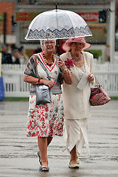 © licensed to London News Pictures. ASCOT, UK.  16/06/11. People arrive at Royal Ascot during a torrential downpour of rain.  Ladies Day at Royal Ascot 16 June 2011. Royal Ascot has established itself as a national institution and the centrepiece of the British social calendar as well as being a stage for the best racehorses in the world. Mandatory Credit Stephen Simpson/LNP