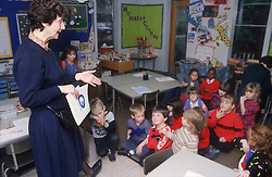 Nursery school teacher and multiracial group of children in classroom,