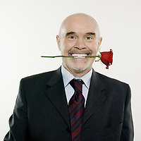studio portrait isolated on white background of a man senior holding a rose flower