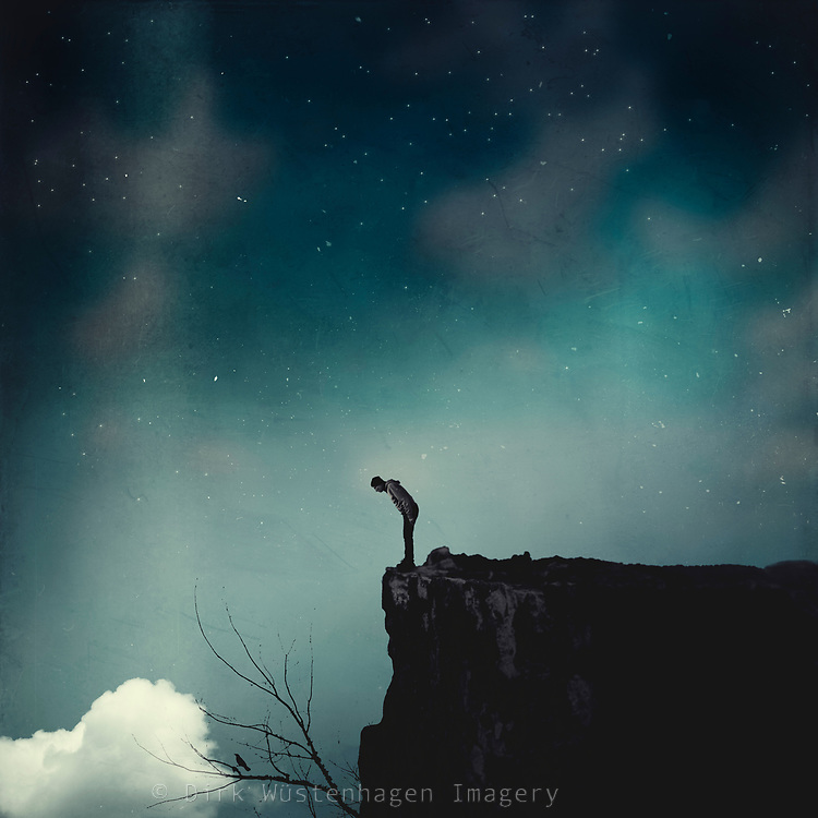 Man standing on a cliff edge looking down - photo composite
