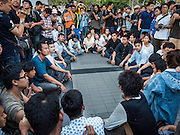 22 MAY 2015 - BANGKOK, THAILAND:   Anti-coup protestors block the sidewalk during a protest in front of the Bangkok Art and Culture Centre Friday evening. The Thai military seized power in a coup on May 22, 2014. There were small protests throughout Bangkok Friday to mark the first anniversary of the coup. Police arrested protestors at several locations. The most serious protest was at Bangkok Art and Culture Centre (BACC) where about 100 protestors, mostly students, faced off against police for several hours. Police made numerous arrests at the BACC protest.   PHOTO BY JACK KURTZ