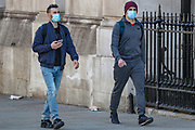 People are seen wearing face protective masks in London, Wednesday, March 25, 2020. British lawmakers voted to shut down Parliament for one month due to the coronavirus outbreak. (Photo/Vudi Xhymshiti)