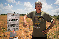 June 11, 2013, Douglas Texas, Landowner Michael Bishop stands next to a warning sign on his property where the Keystone Pipeline has been installed despite his continued battle against it. Michael Bishop has pending court cases against TransCanda alleging fraud. President Obama will decide if the Northern route of the Keystone XL will be permitted before the end of the year.