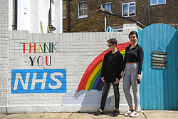 © Licensed to London News Pictures. 02/05/2020. Hammersmith, west London, UK. A mural supporting the work of the NHS during the COVID crisis has appeared on a mews in West London, painted by 12 year old Alex (left) and helped by cousin Chelsea, 28 (right). Photo credit: Guilhem Baker/LNP