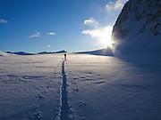 Alaska, Chugach State Park, Eklutna Glacier.  A climber crosses the Eklutna Glacier to approach Peril Peak.