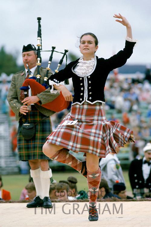 Scottish girl in tartan kilt dancing traditional dance at the Braemar Royal Highland Gathering, the Braemar Games in Scotland