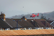 A Welsh Air Ambulance Helicopter arrives over the roof tops into Caerphilly to attend to a patient. Caerphilly, South Wales.  Wales Air Ambulance Charity WAAC is a Charity Air Ambulance service providing free, life-saving Helicopter Emergency Medical Service HEMS for the critically ill and injured of the UK and Wales.