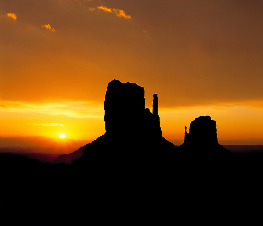 Sunrise light silhouettes The Mittens in Monument Valley, Utah.