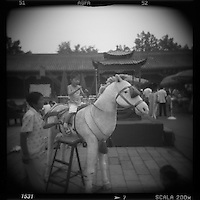 Asia, China, Beijing, Blurred black and white image of young boy posing on fake pony at photo studio in the Forbidden City