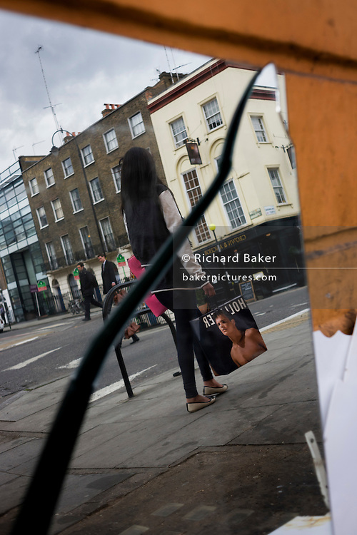 Double image of a woman walking in a street caused by the split, broken mirror lying on the ground with its diagonal crack