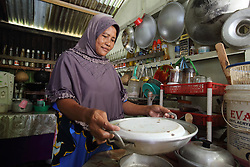 Hasnah 45 yrs in the kitchen of her home home in Lhok Seudu Village where Oxfam had built shelter following the Indian Ocean Tsunami of Dec 2004, District Aceh Besar, Aceh Province, Sumatra, Indonesia