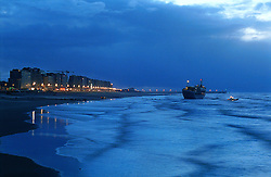 """BLANKENBERGE, BELGIUM - NOVEMBER 9, 2001 - The salvage company Unie Van Redding - En Sleepdienst N.V. waited for the high tide to come in as night fell on the German cargo ship """"Heinrich Behrmann"""", was beached by heavy seas after losing power to the main engine late Thursday night at Blankenberge. The ship was heading for the port at Zeebrugge from Ireland, and was carrying dry cargo, none of which was hazardous. The salvage company Unie Van Redding - En Sleepdienst N.V. was hired to free the ship. Three unsuccessful attempts were made Friday, the second attempt resulted in the injury of two workers when tug boat cables snapped. The beached ship has attracted the attention of curious tourists. (Photo © Jock Fistick)"""