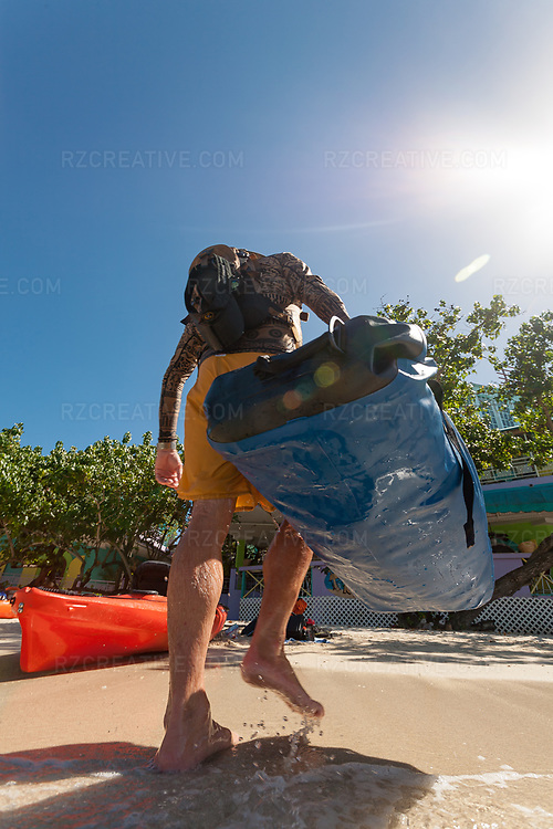 Standup paddler Ted Rutherford unloads his gear at Galge Cove after circumnavigating the island of St. John by paddleboard. © Robert Zaleski / rzcreative.com<br /> —<br /> To license this image contact: robert@rzcreative.com