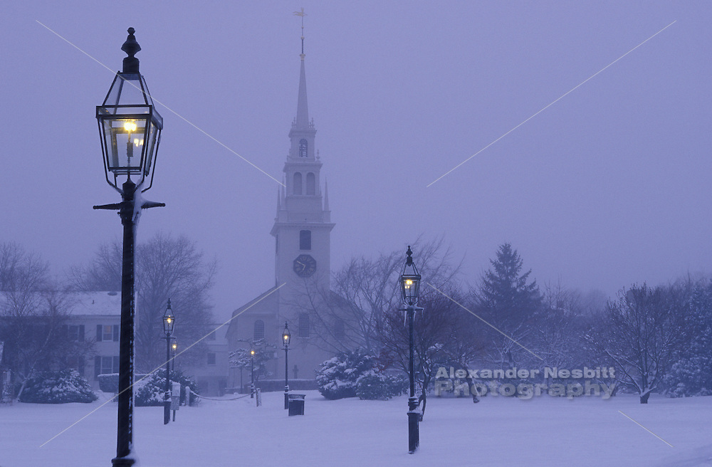 Newport, RI USA - Trinity church on a snowy afternoon with the gas lamps of Queen Anne's square in downtown Newport.