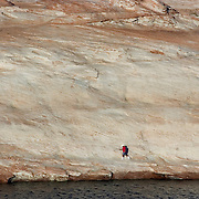 A visitor hikes along the shore of Lake Powell just before Glen Canyon Dam.  The water level on Lake Powell is down over 100 vertical feet and this entire area would be under water if the lake were at its high level.