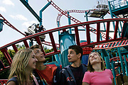 Teenagers in a queue for the Spinball Whizzer ride at Alton Towers Amusement Park, Alton, UK.