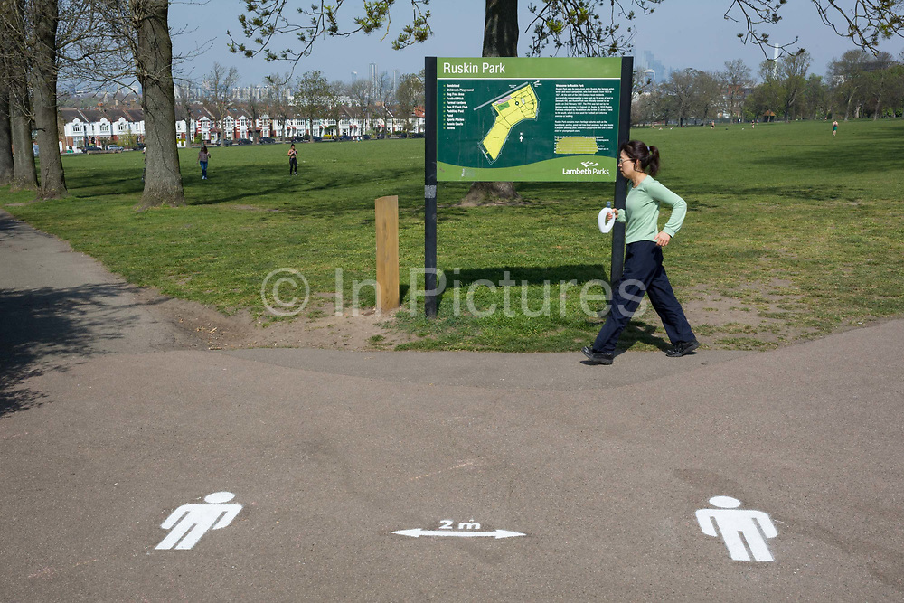 On the first day of the Easter Bank Holiday weekend, and at the end of the second week of lockdown restrictions by the UK government, a lady uses her daily exercise entitlement to spend a warm afternoon near a stencil for keeping 2 metres apart in Ruskin Park in a public green space in the borough of Lambeth, on 10th April 2020, in London, England.
