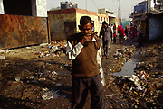 A man covers his mouth as he crosses the open sewers in a main 'street' of Shadipur Depot. The stink is truly horrific and people, with no personal sewer, defecate in the streets. Water is usually stolen by intercepting municipal pipes. Shadipur Depot, New Delhi, India<br /> The Kathiputli Colony in the Shadipur Depot slum is home to hundreds of (originally Rajasthani) performers. The artistes who live here - from magicians, acrobats, musicians, dancers and puppeteers are often international renowed by always return to the Shadipur slum.