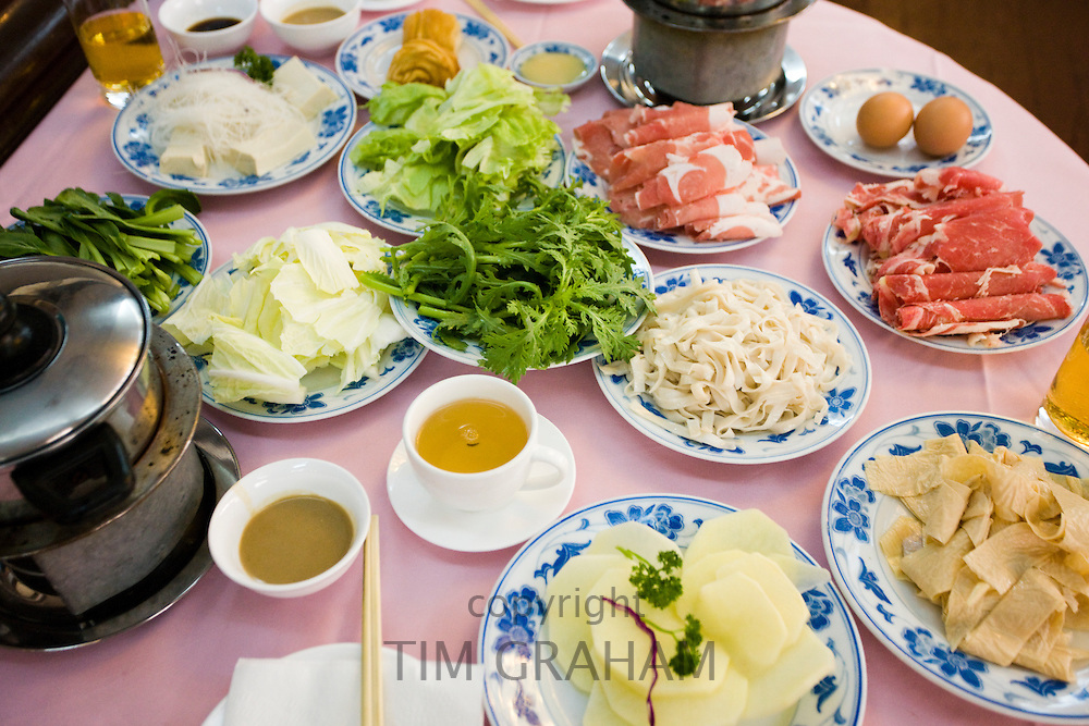 Traditional Chinese Hotpot meal in tourist restaurant, Xian. Diners cook raw meat and vegetables in hot broth