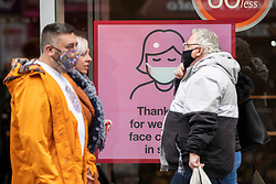© Licensed to London News Pictures. 25/10/2020. Manchester, UK. People wearing face masks pass a sign thanking customers for wearing masks on Market Street, Manchester. Shoppers in Manchester aren't deterred by new tier 3 restriction or potential tier 4 restrictions, which could see retail and restaurants closed. Photo credit: Kerry Elsworth/LNP