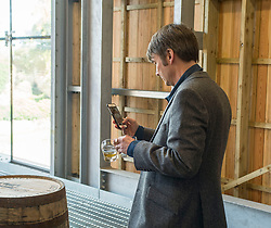 'Rebus' creator Ian Rankin can't resist taking photo mementos of one of the barrels after the author opened Scotland's newest distillery at Lindores Abbey in Fife, which is on the site of the earliest recorded distillation of whisky over 500 years ago.<br /> © Dave Johnston/ EEm