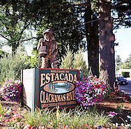 A street corner in downtown Estacada Oregon features a logger carved out of wood atop the town's sign.