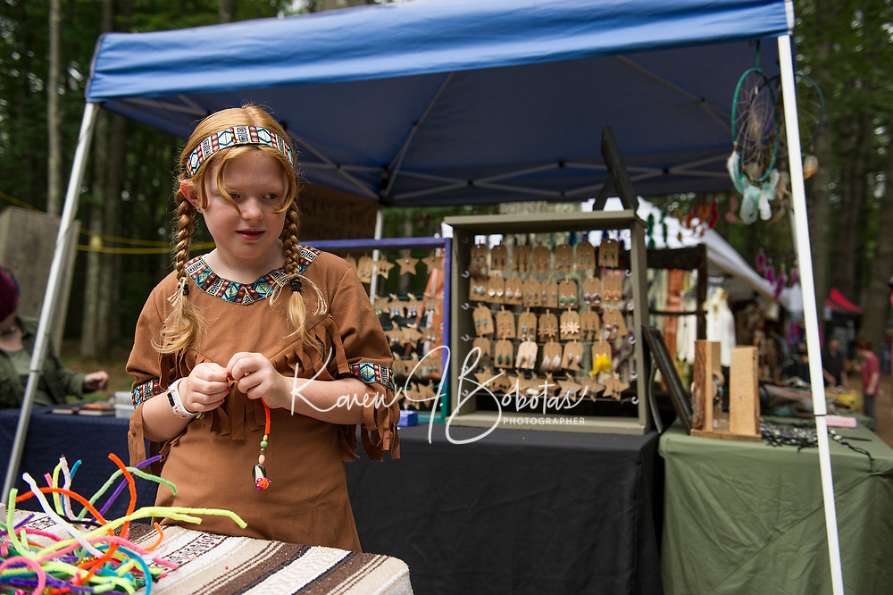 Ailia Garnham of Mont Vernon makes a beaded necklace during her first visit to the Labor Day Pow Wow with the Laconia Indian Historical Association on Saturday.  (Karen Bobotas/for the Laconia Daily Sun)