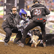 An injured rider is helped from the track during the Monster Energy AMA Supercross series held at MetLife Stadium. 62,217 fans attended the event held for the first time at MetLife Stadium, New Jersey, USA. 26th April 2014. Photo Tim Clayton