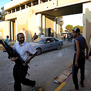 A libyan man passes by carrying several assault weapons looted from Muammar Gaddafi's Bab Al Azizia compound in Tripoli.