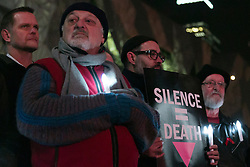 © Licensed to London News Pictures. 22/07/2014.  A man holds up a sign reading 'Silence = Death' during a candlelight vigil at Federation Square in Melbourne, Australia. At least six delegates travelling to the 20th International AIDS Conference were on board the Malaysia Airlines flight MH17. Photo credit : Asanka Brendon Ratnayake/LNP