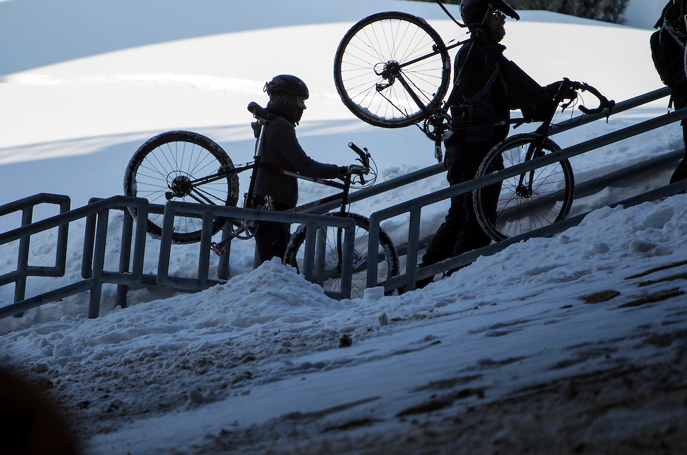 Racers walk their bikes up the stairs from under the Hennepin Avenue bridge as they begin Stupor Bowl 17 in Minneapolis February 1, 2014.