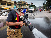 24 JANUARY 2018 - GUINOBATAN, ALBAY, PHILIPPINES:  A firefighter hoses down the main street after an ash fall covered the roads in Guinobatan. The Mayon volcano continued to erupt Tuesday night and Wednesday forcing the Albay provincial government to order more evacuations. By Wednesday evening (Philippine time) more than 60,000 people had been evacuated from communities around the volcano to shelters outside of the 8 kilometer danger zone. Additionally, ash falls continued to disrupt life beyond the danger zones. Several airports in the region, including the airport in Legazpi, the busiest airport in the region, are closed indefinitely because of the amount of ash the volcano has thrown into the air.   PHOTO BY JACK KURTZ