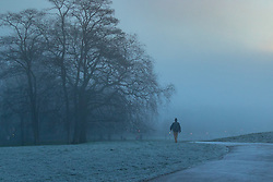 Primrose Hill, London, December 28th 2016. A cold, frosty and misty dawn greets London as seen from Primrose Hill, with the fog rolling in at around sunrise, obliterating the city's skyline and giving rise to soft, diffused tones. PICTURED: A walker heads down Primrose Hill as the sunlight begins to penetrate the mist.