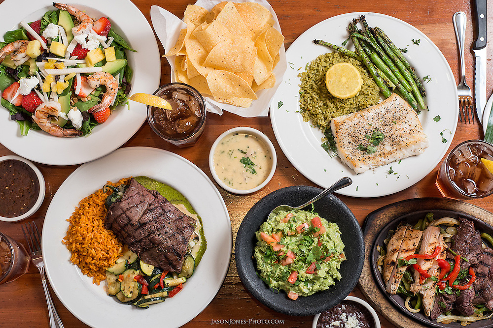 Overhead view of a table setting at a Mexican food restaurant for multiple people. Featured are popular menu items such as Fajitas, Guacamole, Fish, Shrimp, Rice, Carne Asada, Queso and refried beans