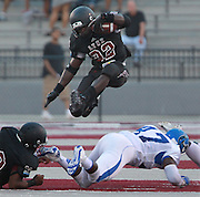 Lindenwood-Belleville player Kameron Harris (22) from East St. Louis, leaps over a Culver-Stockton would-be tackler, Marquavious Brown (47) early in the game.