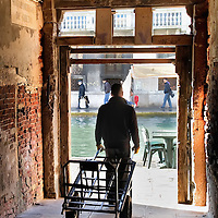 "VENICE, ITALY - NOVEMBER 15:  A porter leaves the ghetto from the ""sotoportego"" that is a link beween teo streets, with ghetto a sign displayed on the wall  on November 15, 2011 in Venice, Italy. Established in 1516 the Ghetto of Venice was the area were Jews were compelled to live during the Venetian Republic. The English term 'ghetto' is derived from the Venetian term for 'slag' and refers to the refuse left the foundry that was located on the same island. In present times the ghetto is a multi-ethnical area area seen as the cultural heart of the city, but with five synagogues remains the centre of the of Jewish community."