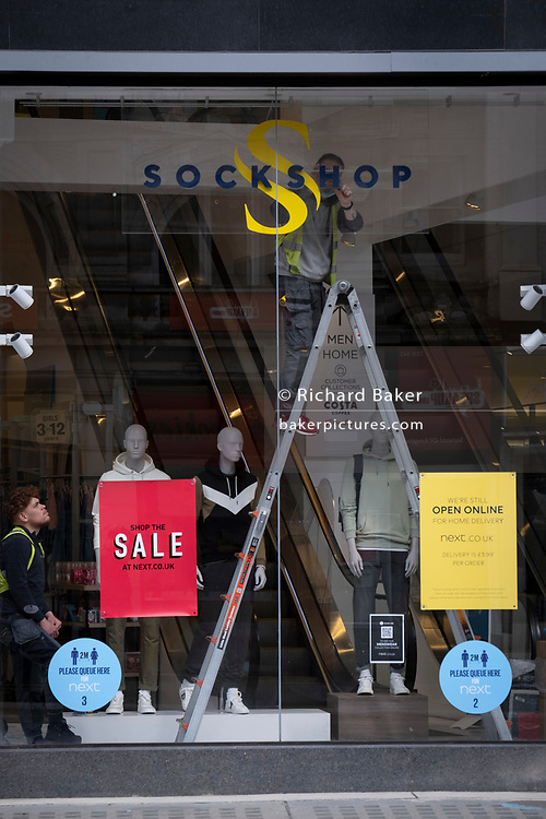 Days before the third Coronavirus lockdown ends, and non-essential retailers and shops re-open again, shop fitters adjust signage in the window of the Sockshop retailer on Oxford Street, on 9th April 2021, in London, England.